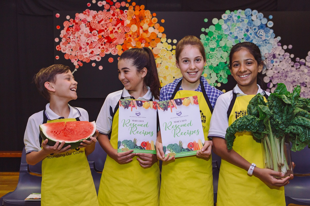 Four OzHarvest FEAST students - the boy is holding a watermelon, two girls holding cookbooks and another girl holding silverbeet