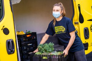 OzHarvest food rescue driver wearing a mask lifting a crate of food into the van