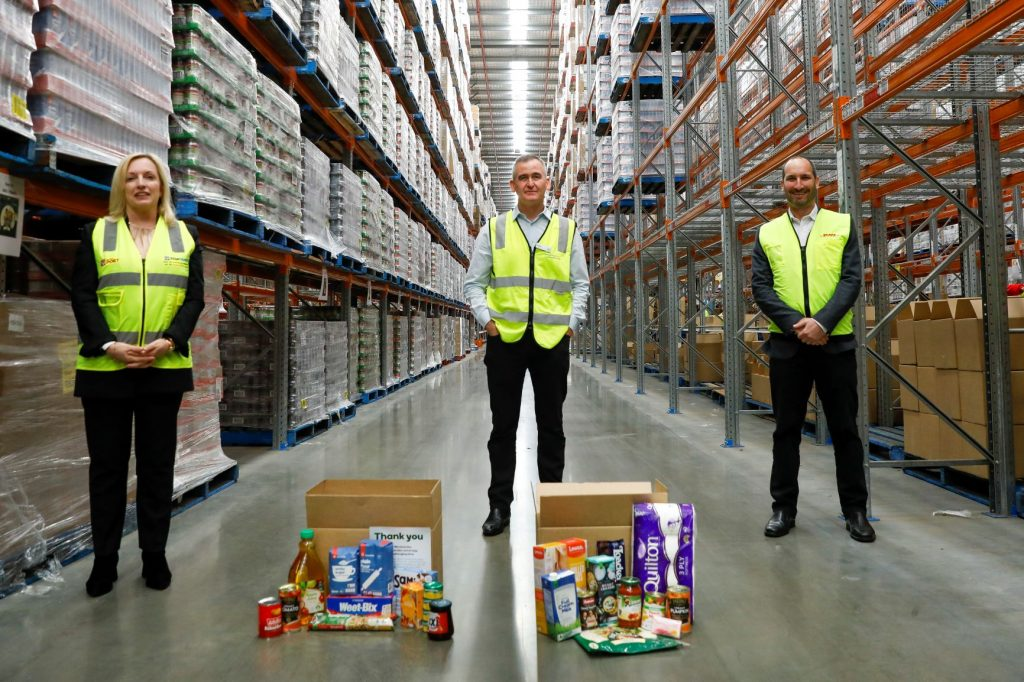 Christine Holgate, Brad Banducci and Saul Resnick standing in a warehouse with 'Woolworths Basics Box'